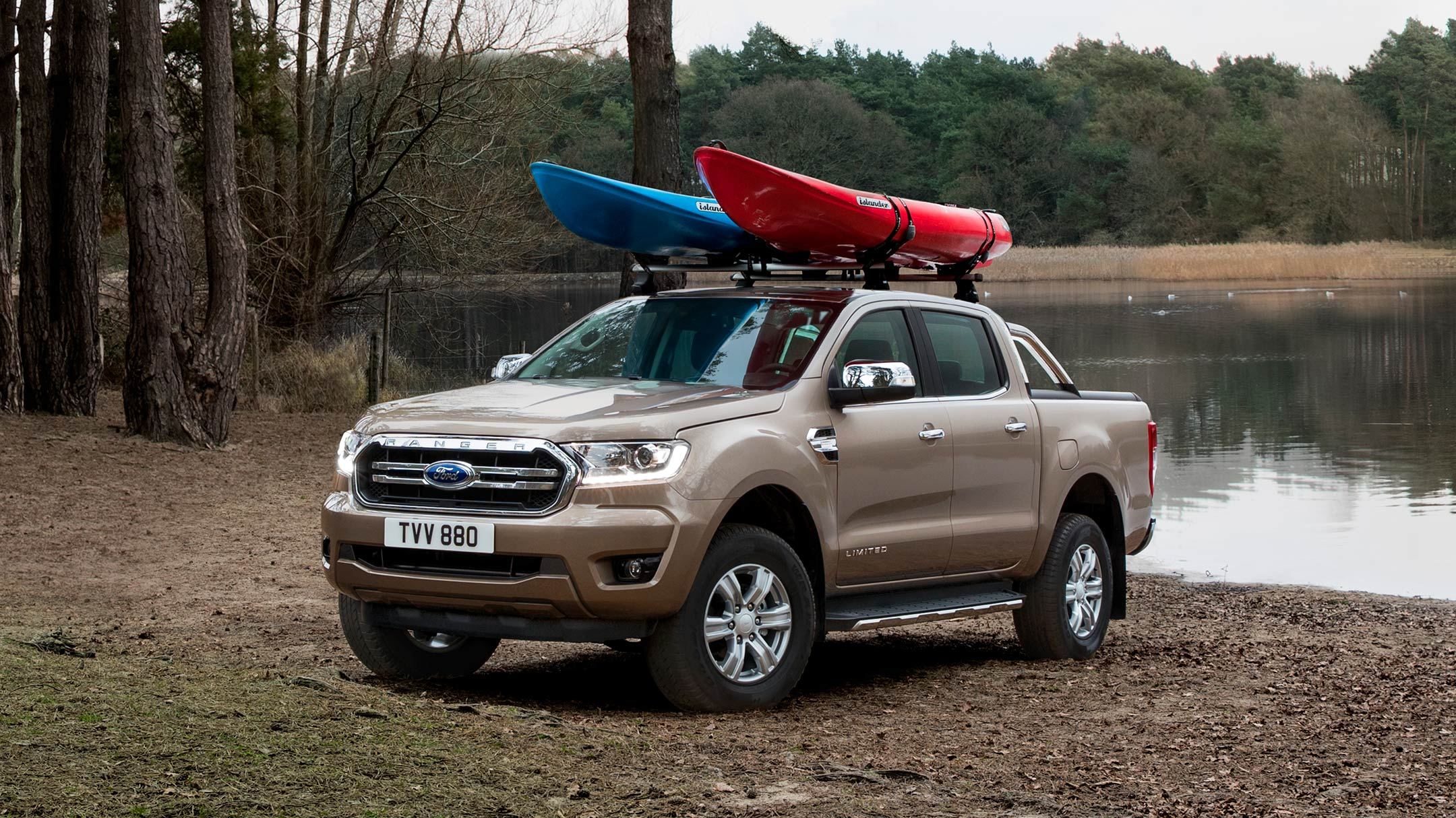 Silver Ford Ranger Wildtrak loaded with canoes parked near lake