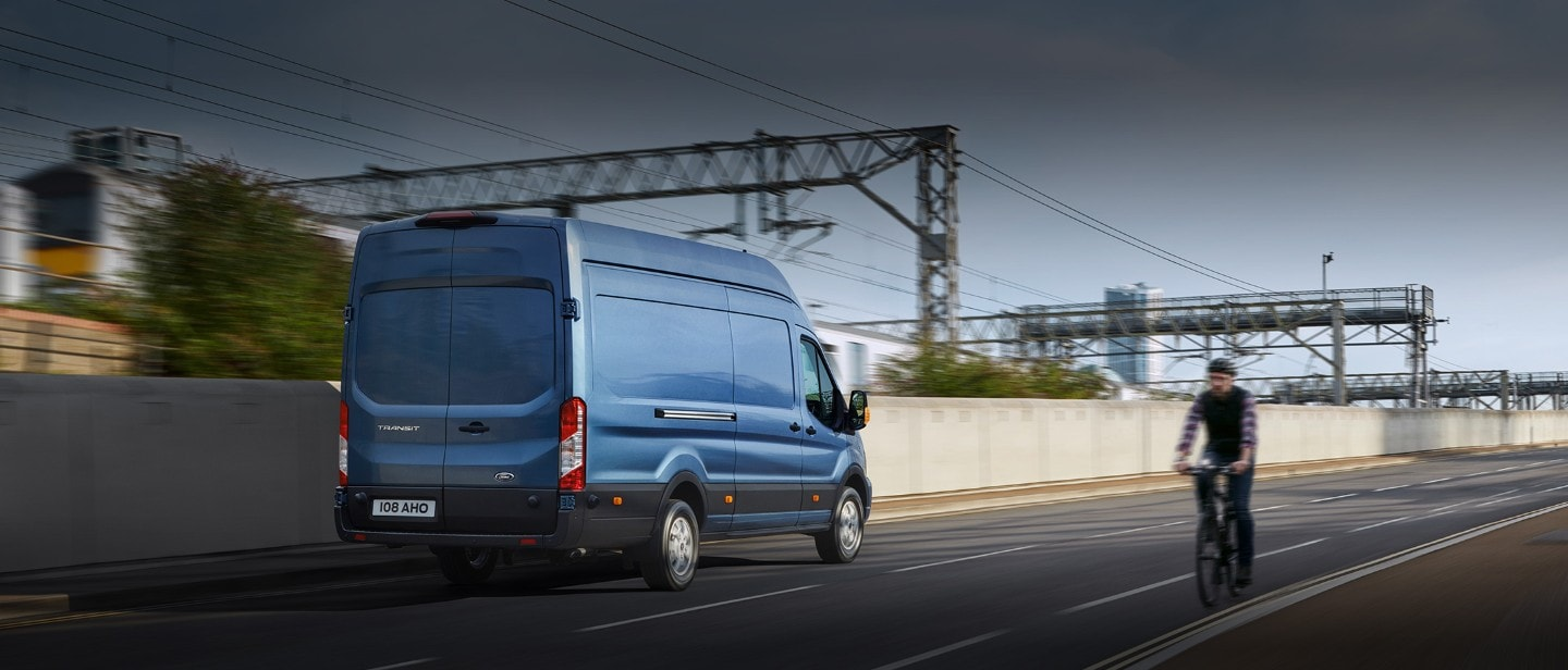 New Blue Ford Transit Van rear view on road