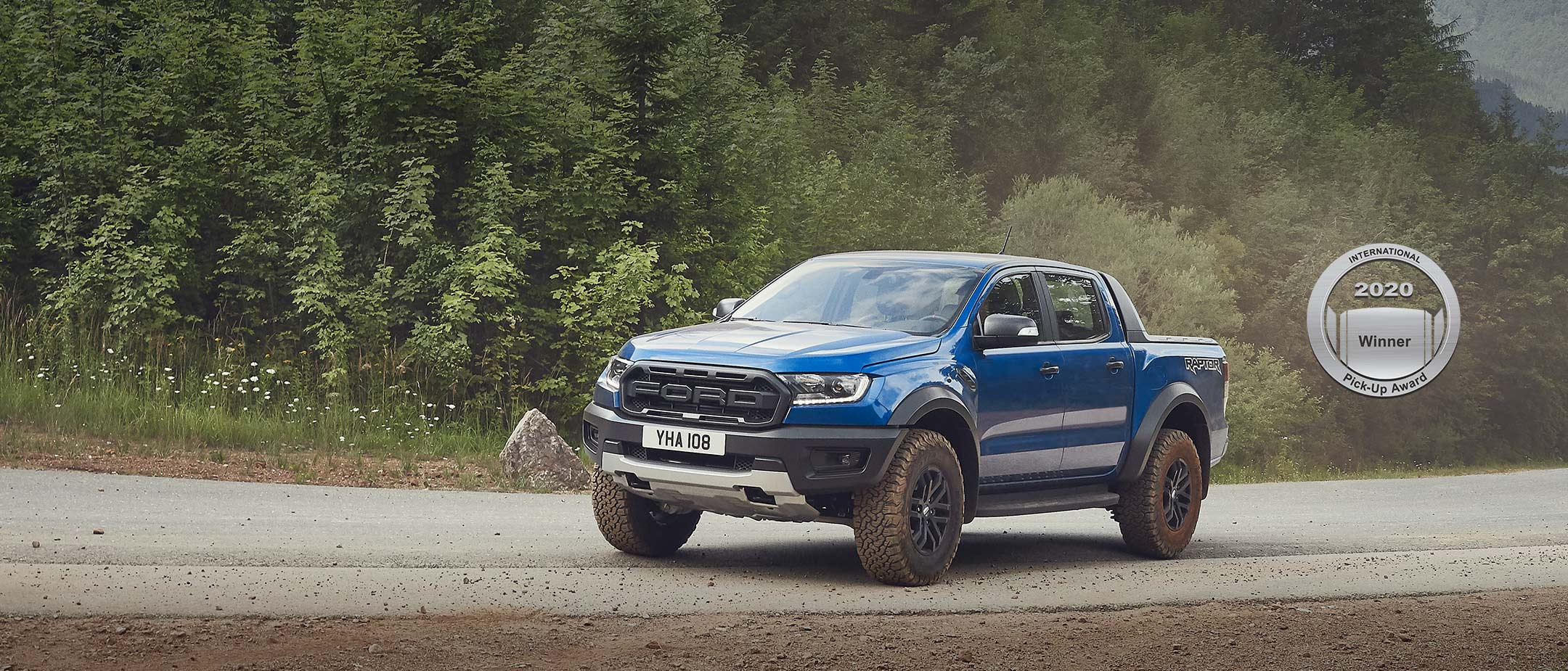 Blue Ford Ranger Raptor driving through a countryside, front three quarter view