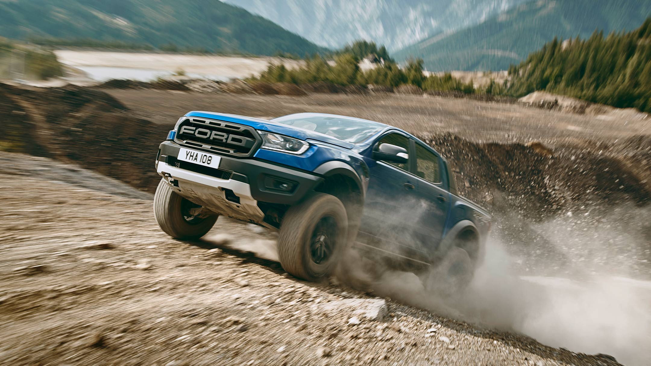 Blue Ford Ranger Raptor driving uphill off road